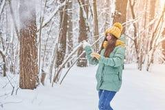 Красивая маленькая девочка в связанной шляпе, играя в снеге в лесе Стоковое Изображение RF