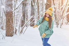 Красивая маленькая девочка в связанной шляпе, играя в снеге в лесе Стоковое фото RF