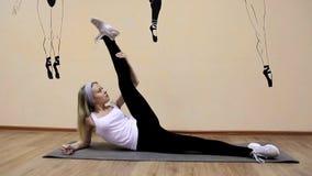 Красивая маленькая девочка в sportswear делает тренировки на лежать расшир видеоматериал