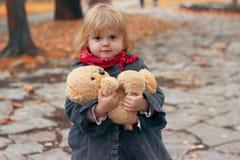 Красивая маленькая девочка держа ее плюшевый мишку в парке, на холодный день осени; стоковые изображения