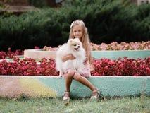 Красивая маленькая девочка держа смешную пушистую собаку Ребенок имея потеху на запачканной естественной предпосылке счастье прин Стоковое Изображение RF