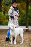Красивая маленькая девочка играя с собакой outdoors Концепция любимчика Стоковая Фотография