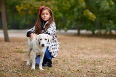 Красивая маленькая девочка играя с собакой outdoors Концепция любимчика Стоковые Изображения