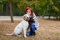 Красивая маленькая девочка играя с собакой outdoors Концепция любимчика Стоковые Изображения RF