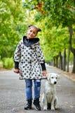 Красивая маленькая девочка идя с собакой outdoors Концепция любимчика Стоковые Фотографии RF