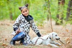 Красивая маленькая девочка идя с собакой outdoors Концепция любимчика Стоковое фото RF