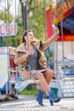 Красивая маленькая девочка имея потеху и смеясь над в парке атракционов Стоковое Изображение RF