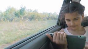 Красивая маленькая девочка использует таблетку с открытой цифровой картой в ей, говорить и усмехаться усаживание движения девушки акции видеоматериалы