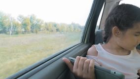 Красивая маленькая девочка использует таблетку с открытой цифровой картой в ей, говорить и усмехаться усаживание девушки предназн видеоматериал