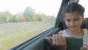 Красивая маленькая девочка использует таблетку с открытой цифровой картой в ей, говорить и усмехаться усаживание девушки предназн сток-видео