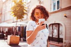 Красивая маленькая девочка используя умный телефон и слушающ к музыке идя на улицу Стоковые Фотографии RF