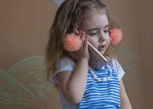 Красивая маленькая девочка и отрезки провода держа телефон вызывают к кто-нибудь Серый цвет предпосылки стоковые фото