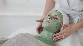 Красивая маленькая девочка на beautician делает процедуры по спа Рука cosmetologist прикладывает зеленую маску на видеоматериал