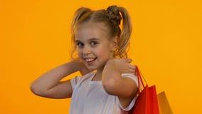 Красивая маленькая девочка подмигивая на камере и показывая красные хозяйственные сумки, скидки видеоматериал
