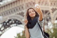 Красивая маленькая девочка принимая смешное selfie с ее мобильным телефоном около Эйфелевой башни стоковые фото