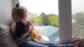 Красивая маленькая девочка при кукла сидя на силле окна видеоматериал