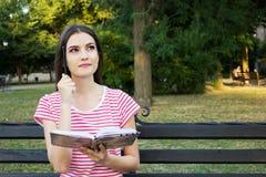 Красивая маленькая девочка сидя на деревянной скамье в парке и думая с книгой и ручка помещенная ее головой Стоковое Изображение RF