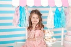 Красивая маленькая девочка сидя на таблице с конфетами Бар дня рождения конфеты Портрет крупного плана стороны младенца Немногое  стоковое фото