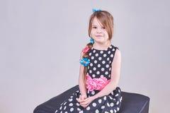 Красивая маленькая девочка сидя на черном кубе Стоковое фото RF