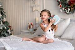 Красивая маленькая девочка сидя около рождественской елки Стоковые Изображения RF