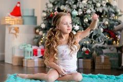 Красивая маленькая девочка сидя около рождественской елки Стоковое Фото