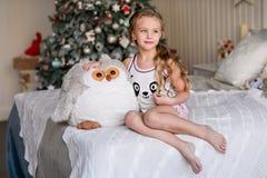 Красивая маленькая девочка сидя около рождественской елки Стоковые Фотографии RF