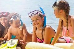 Красивая маленькая девочка среди друзей на пляже Стоковые Изображения