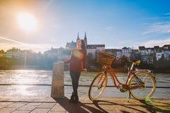 Красивая маленькая девочка стоит на обваловке около велосипеда города с корзиной красного цвета в Швейцарии, городе Базеля солнеч Стоковые Фотографии RF