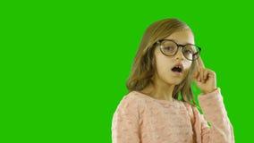 Красивая маленькая девочка с длинным вьющиеся волосы около 8 или 10 со стеклами выражает ее наслаждение и показывает что она акции видеоматериалы