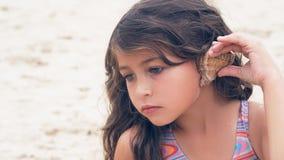 Красивая маленькая девочка с длинным вьющиеся волосы слушая к музыке моря в cockleshell на пляже Стоковое Изображение RF