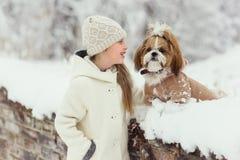 Красивая маленькая девочка с ее собакой на снеге в зиме стоковое изображение rf
