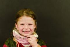 Красивая маленькая девочка с стеклами на черной предпосылке Смешная милая девушка с стеклами Малая девушка носит красочный свитер Стоковые Фотографии RF