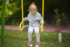 Красивая маленькая девушка redhead ехать качание на спортивной площадке стоковые изображения