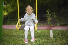 Красивая маленькая девушка redhead ехать качание на спортивной площадке стоковые изображения rf