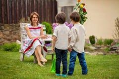 Красивая мама, имеющ кофе в задворк, молодое милое giv ребенка Стоковое Изображение RF
