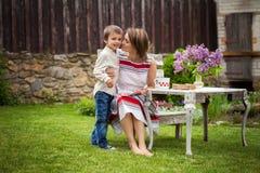 Красивая мама, имеющ кофе в задворк, молодое милое giv ребенка Стоковые Изображения RF