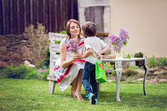 Красивая мама, имеющ кофе в задворк, молодое милое giv ребенка Стоковое фото RF