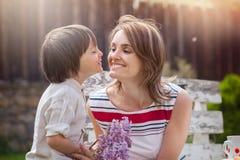 Красивая мама, имеющ кофе в задворк, молодое милое giv ребенка Стоковая Фотография RF
