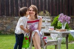 Красивая мама, имеющ кофе в задворк, молодое милое giv ребенка Стоковые Изображения