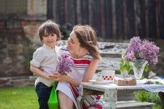 Красивая мама, имеющ кофе в задворк, молодое милое giv ребенка Стоковая Фотография