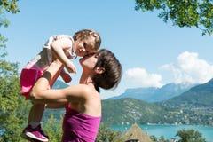 Красивая мама объятие к ее дочери в природе стоковые изображения