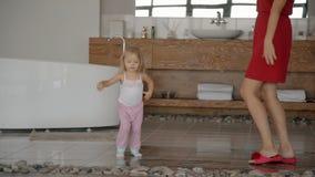 Красивая мать в красных одеждах и прелестная маленькая девочка танцующ и скачущ в bathroom с утесом акции видеоматериалы