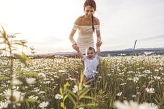 Красивая мать идет на поле с маленьким ребёнком стоковое фото