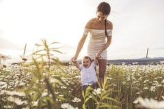Красивая мать идет на поле с маленьким ребёнком стоковое изображение rf