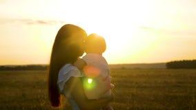 Красивая мать идет с ее маленькой дочерью и держит младенца в ее оружиях Счастливая семья отдыхая в парке летом внутри сток-видео