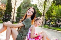 Красивая мать и дочь сидя спина к спине и играя в парке Стоковые Изображения