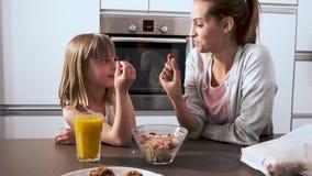 Красивая мать и ее дочь принимая и есть хлопья шара в кухне дома акции видеоматериалы