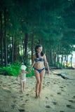Красивая мать идя с маленькой дочерью вдоль пляжа Стоковая Фотография
