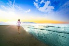 Красивая маленькая девочка бежать и играя бортовое море на песке стоковые фото