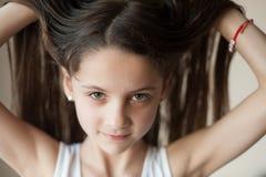 Красивая маленькая девочка выправляет ее волосы стоковая фотография